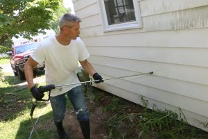 pressure washing the siding of a house